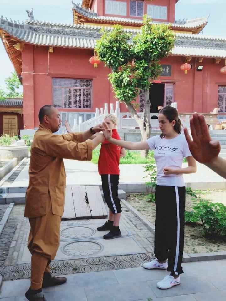 мастер ши янчен тренирует иностранцев в монастыре солнечный день красные стены
