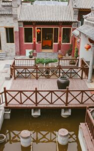 пруд на территории монастыря с зотолыми рыбками, фонтан, красные стены, деревянный мост