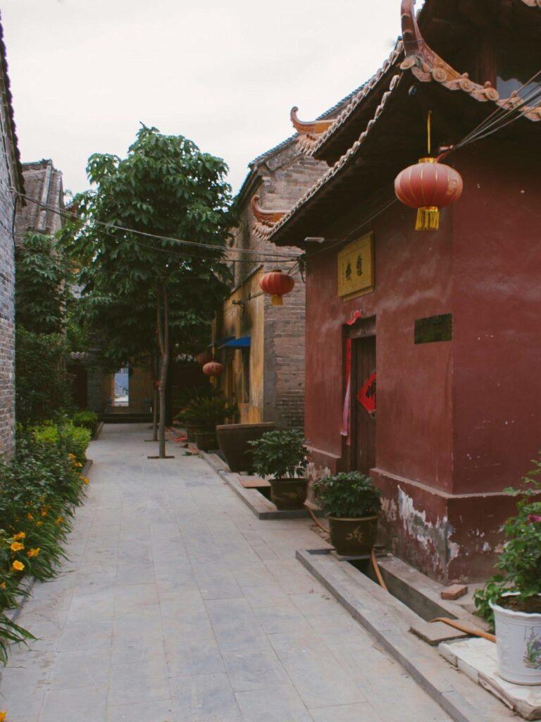 Узкая улочка на территорияя китайского храма монастыря красные стены и красный фонарь зелёные кусты